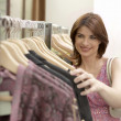 Woman looking through line of clothes hanging in a fashion store. - Stock Photo