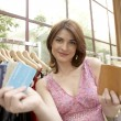 Woman showing a credit card while standing in a fashion store. — Stock Photo #19805219