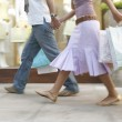 Stock Photo: Couple walking down shopping street with shopping bags, holding hands.