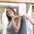 Portrait of a young woman holding shopping bags standing by a fashion store. — Foto Stock