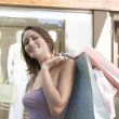 Portrait of a young woman holding shopping bags standing by a fashion store. — Stockfoto