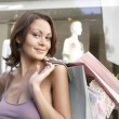 Portrait of a young woman holding shopping bags standing by a fashion store, smiling. — Stock Photo
