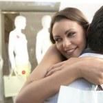młoda kobieta przytulanie człowiek poza sklep odzieżowy — Zdjęcie stockowe