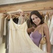 Portrait of a young attractive woman holding a garment in a fashion store. — Stock Photo #19805691