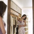 Young attractive woman trying on a dress in a fashion store, looking at her reflection in a mirror. - Stock Photo