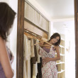 Stock Photo: Young attractive woman trying on a dress in a fashion store, looking at her reflection in a mirror.