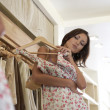 Close up of a young attractive woman trying on a dress in a fashion store - Stock Photo