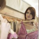verfijnde vrouw kijken naar zichzelf in de spiegel van een winkel, terwijl een jurk voor haar — Stockfoto