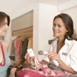 Female client shopping at fashion store with shop assistant reading a label with a barcode reader. — Foto de Stock