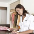 Attractive shop assistant calculating sales by store desk. — Stock Photo #19806725