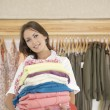 Shop assistant holding a pile of clothes in a fashion store — Стоковая фотография
