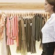 Blured figure of a sophisticated store assistant walking through a fashion store. — Stock Photo #19807103