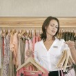 Young store attendant ordering hangers with clothes in a fashion store. - Stock Photo
