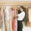 Female store attendant arranging a line of clothes in a fashion store. — Foto de Stock