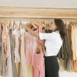 Female store attendant arranging a line of clothes in a fashion store. - Stock Photo