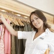 Stock Photo: Close up of store assistant sorting clothes on store's rails, smiling.