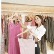Store assistant sorting clothes on store's rails, smiling. - Stock Photo