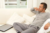 Man with a laptop computer sitting on a white sofa at home. — Stock Photo
