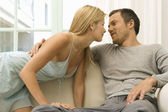 Sexy young couple kissing on home's sofa — Stock Photo