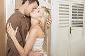 Young passionate couple kissing in a home's bedroom. — Stok fotoğraf