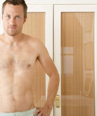Attractive young man standing by wardrobe doors in a bedroom in underwear — Stock Photo