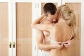 セクシーなカップルはハグ、キスの寝室。男脱いでいる女性. — ストック写真