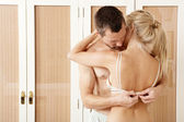 Sexy couple hugging and kissing in bedroom. Man undressing woman. — Stock fotografie