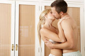 Sexy young couple passionately hugging in bedroom. — Stock Photo