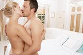 Cerca de una pareja desnuda besos en dormitorio. — Foto de Stock