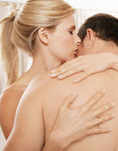 Close up of a nude couple kissing in a bedroom. — Stock Photo