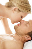 Sexy young couple sensually kissing in bed — Stock Photo
