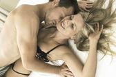 ベッドでは、キス、魅力的な若いカップルの肖像画閉じる笑みを浮かべて. — ストック写真