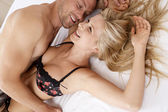 セクシーなカップルはキスをし、ベッドの中で遊んでのクローズ アップ. — ストック写真