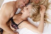 Närbild på ett sexigt par kyssas och spelar i sängen. — Stockfoto