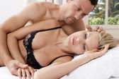 Romantic couple in bed, with man caressing woman's hair. — Stock Photo