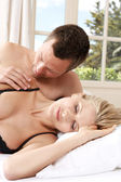 Romantic couple in bed, with man caressing woman's shoulder. — Stock Photo