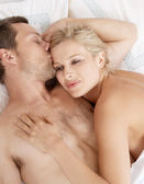 Young attractive man kissing woman's forehead in bed. — Stock Photo