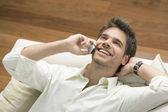 Professionele jongeman met behulp van een mobiele telefoon terwijl vaststelling op een sofa. — Stockfoto