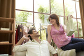 Woman offering a newly bought gift to her boyfriend in fashion store. — Stock Photo
