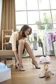 Ung sofistikerad kvinna tryin på nya skor i en modebutik — Stockfoto