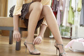Close up of a young sophisticated woman tryin on new shoes in a fashion store. — Stock Photo