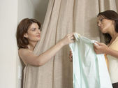 Sophisticated woman in fitting room, handing over a garmet to the shop assistant. — Stock Photo