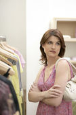 Young woman being undecisive in a fashion store. — Stock Photo