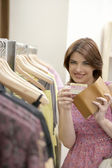 Young woman holding a credit card in a fashion store. — Stock Photo