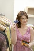 Jovem mulher mostrando um cartão de crédito quando se encontrar em uma loja de moda. — Foto Stock