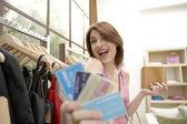 Jovem mulher exibindo seus cartões de crédito em pé em uma loja de moda. — Foto Stock