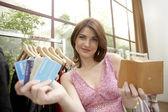 Mujer mostrando una tarjeta de crédito mientras esté parado en una tienda de moda. — Foto de Stock