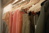 Detail of clothes hanging on wooden hangers in a fashion store. — Stock Photo