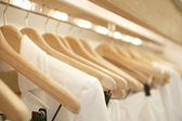 Detail of white clothes hanging on wooden hangers in a fashion store. — Stock Photo