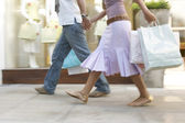 Couple walking down a shopping street with shopping bags, holding hands. — Stock Photo